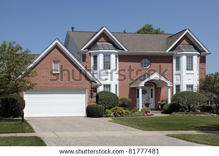 Brick home with columns and arched entry - stock photo