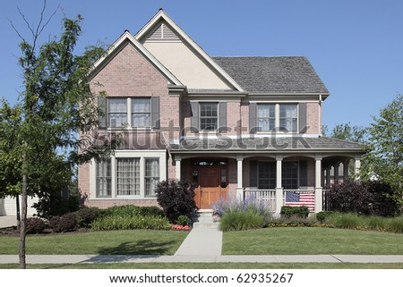 Brick home with front porch and cedar roof - stock photo