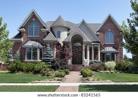 Brick home with turret and arched entry - stock photo