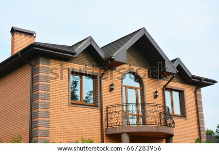Brick House Construction With Different Types Of Roof Design And Metal  Balcony. Roofing Construction.