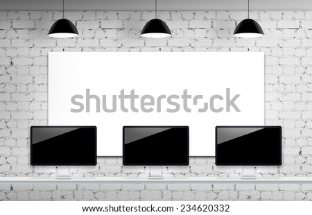 Brick interior with three computer displays on a table - stock photo