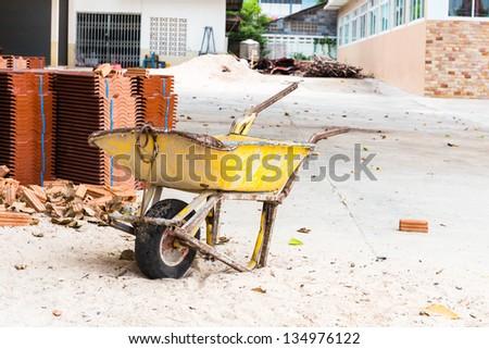 Brick Mason's Wheelbarrow on construction sit - stock photo