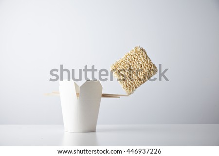 Brick of dry noodles balances on the edge of chopsticks on blank takeaway box isolated on white commercial retail set mockup - stock photo