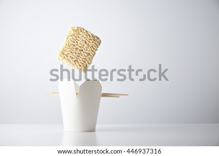 Brick of dry noodles falls down inside blank takeaway box with chopsticks isolated on white commercial retail set - stock photo