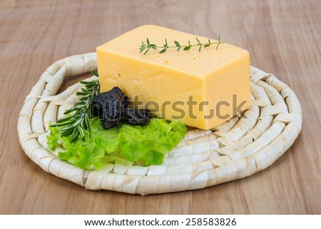 Brick of yellow cheese with thyme and plum - stock photo