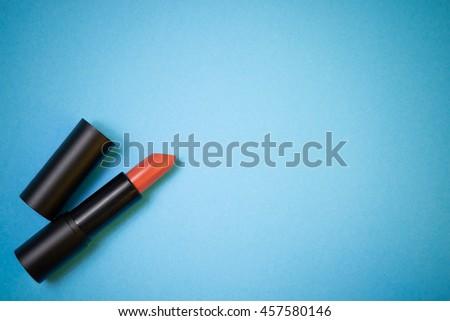Brick orange shade lipstick for make up on blue background. - stock photo