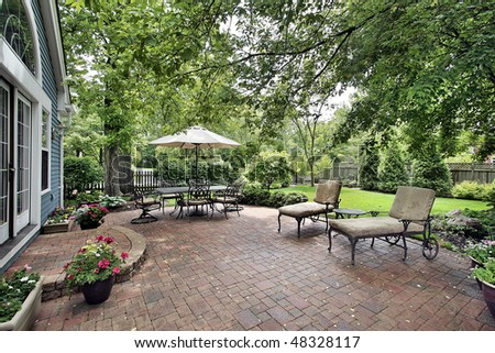 Brick patio with table umbrella and chairs - stock photo