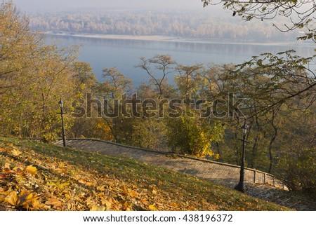 Brick-paved Path and Lanterns on Hillslope under Morning Sun on Autumn Day - stock photo