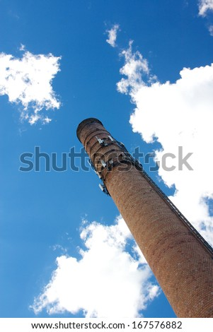 Brick smoke stack with cel phone antennas rises into the blue sky before the camera. - stock photo