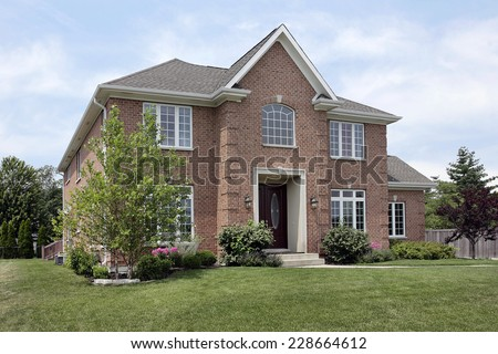 Brick suburban home with arched window above entry - stock photo