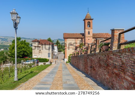 Brick wall along cobblestone walkway and parish church on background under blue sky in Piedmont, Northern Italy.