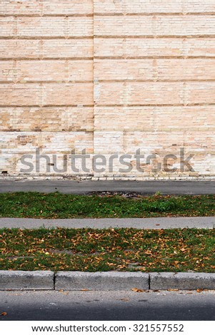 Brick wall and the road in the foreground - stock photo