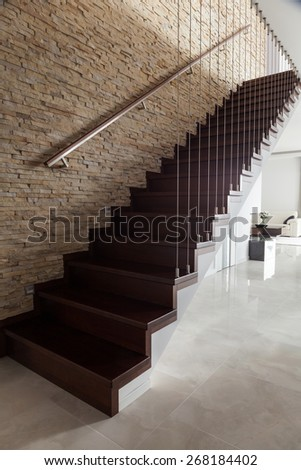 Brick wall and wooden stairs in designed interior - stock photo