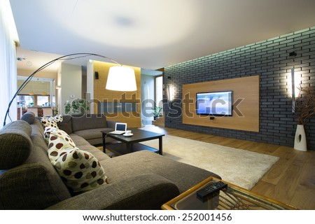 Brick wall in modern spacious drawing room - stock photo