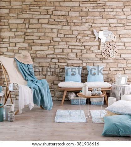 brick wall lounge chair blue pillow and hat old rock relax decor - stock photo