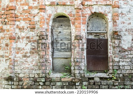brick wall of the old destroyed building with the broken window niches - stock photo