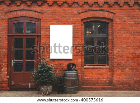 Brick wall restaurant facade with window, entrance, christmas decor and blank space for menu poster.  - stock photo