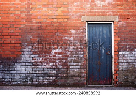 Brick wall with a door - stock photo