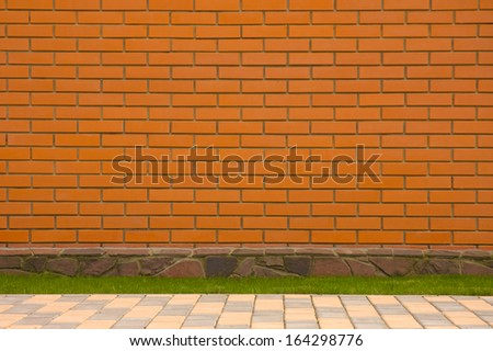 Brick wall with a stone border and green grass