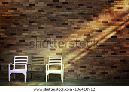 Brick wall with chairs and lighting - stock photo