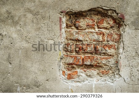 Brick wall with crumbling plaster on old building. - stock photo