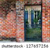 Brick Wall With Gate To Courtyard In New Orleans French Quarter - stock photo