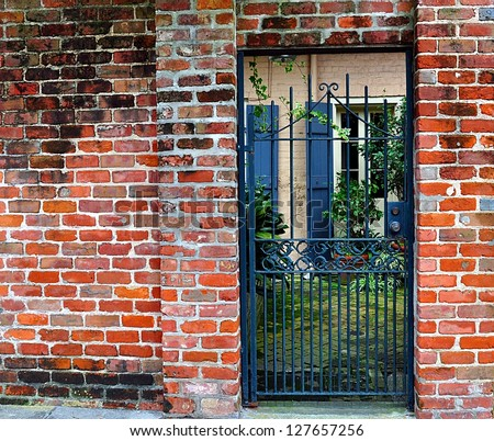 Brick Wall With Gate To Courtyard In New Orleans French Quarter