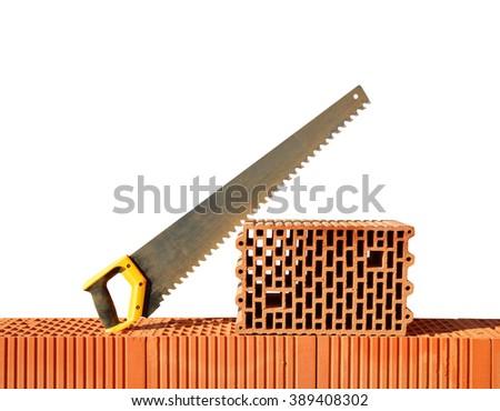 Brick wall with handsaw on bricks. Bricklaying work. - stock photo