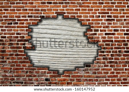 brick wall with hole and wooden board - stock photo