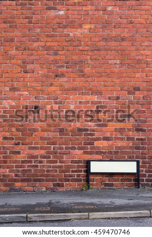 Brick wall with pavement and sign in front