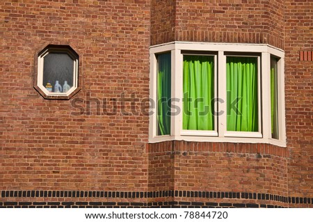 Brick wall with window and green curtain. The window is closed. - stock photo