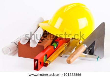 brick, yellow hard hat, tools and construction plans on white background - stock photo