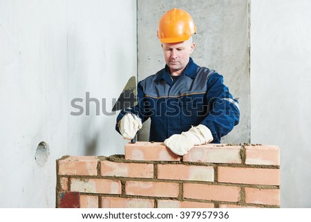 bricklayer at work with red brick  - stock photo