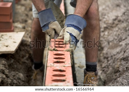 Bricklayer building a wall - stock photo