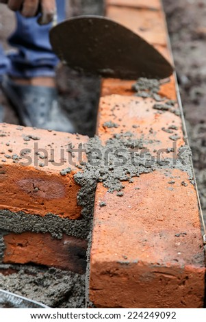 bricklayer. Construction worker using tools to build a brick wall - stock photo