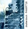 """Bricklayer's labourer in an English village - photo from """"Great War"""" magazine, vol. 156, UK, circa 1917 - stock photo"""