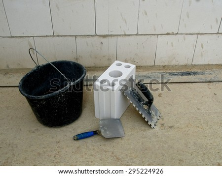 Bricklayer set on the concrete background (bucket, air brick and trowels) - stock photo