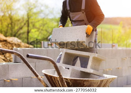 Bricklayer taking another brick from a wheelbarrow - stock photo