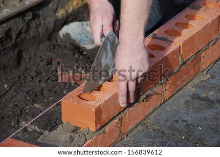Bricklayer using trowel to tap a brick level - stock photo