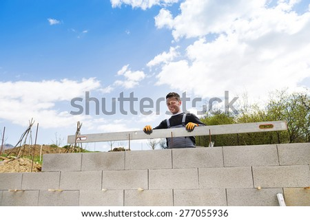 Bricklayer with a level checking another row of bricks - stock photo