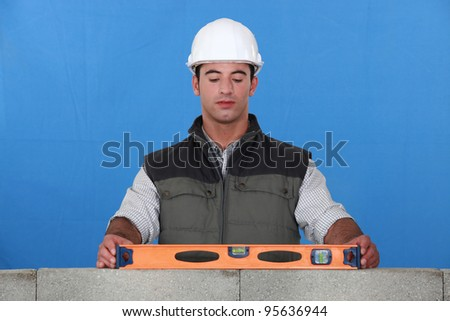 Bricklayer with a spirit level - stock photo