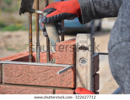 Bricklayer Worker Installing Red Clinker  Blocks and Caulking Brick Masonry Joints Exterior Wall with Trowel putty Knife  and Fixing with Spirit Level Outdoor - stock photo