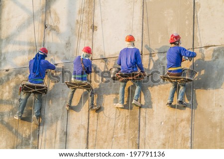 Bricklayer working on the high building - stock photo