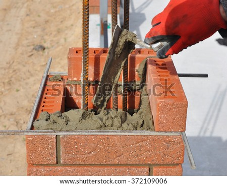 Bricklaying closeup. Bricklayer hand holding a putty knife and building a brick fence column with iron bar. - stock photo