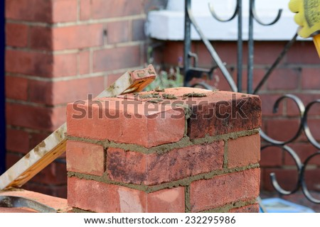 Bricklaying - spirit level resting against wall - stock photo