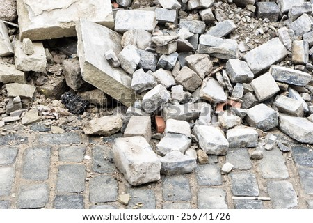 Bricks and rubble on a cobbled road - stock photo