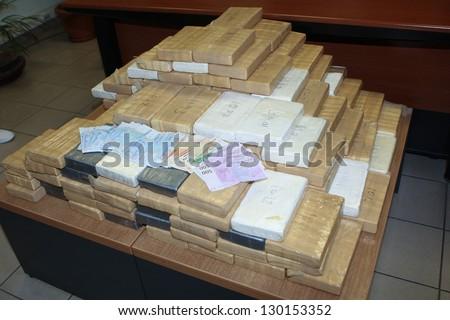 bricks of cocaine and money - stock photo