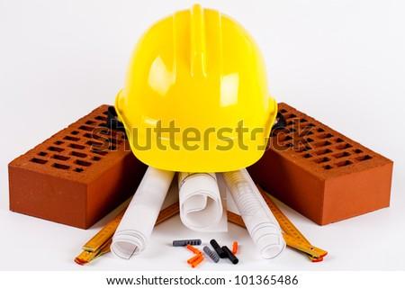bricks, yellow hard hat, tools and construction plans - stock photo