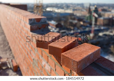 Brickwork in the new house with three bricks in the foreground - stock photo