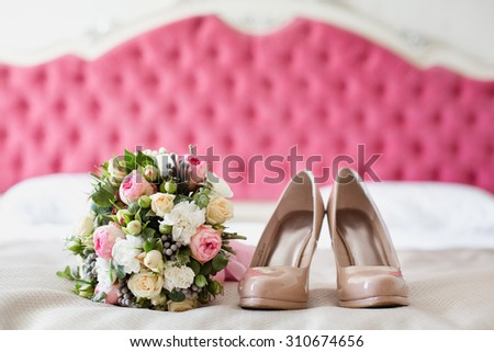 Bridal accessories: beige shoes and bride's bouquet on a bed with pink background - stock photo
